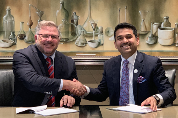 Jeff Watson and Dr Shamsheer Vayalil sign the agreement