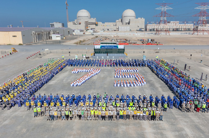 Enec officials and workers celebrate the achievement